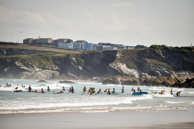 Surfers play in the waves during the hot sunshine on Tolcarne beach in Newquay, Cornwall, the week before school holidays, as more hot weather is due to hit the UK this week (Ben Birchall/PA)