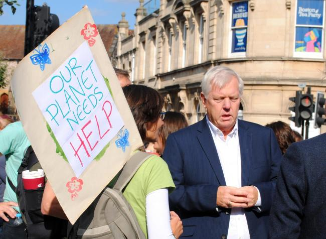 A climate protest holding a placard near to Somerset County COuncil leader David Fothergill