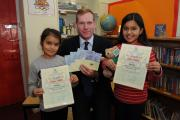Alicia Valmiki (right) and her sister Rihanna Valmiki receive the prize for the winning design for Jeremy Browne's 2014 Christmas card competition.